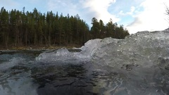 Ice cold mountain creek stream with massive ice buildup flowing into river Stock Footage