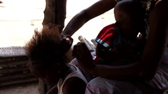 Mother taking care of the hair of her child -Africa village Stock Footage