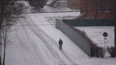 Man walks on road in snow Stock Footage