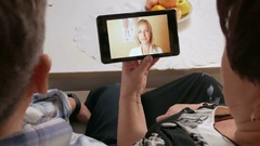 Elderly couple receives doctor consultation for tablet PCs. Man coughs and the Stock Footage