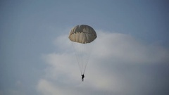 Paratrooper landed on the grass and blue sky with clouds, white parachute Stock Footage