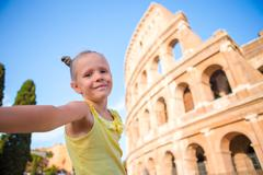 Little girl taking selfie in front of Colosseum in Rome, Italy Stock Photos