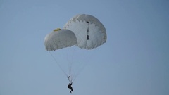 Paratrooper with an open reserve parachute landed on the grass Stock Footage