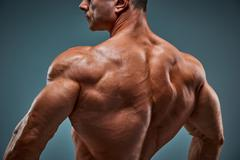 Torso of attractive male body builder on gray background Stock Photos