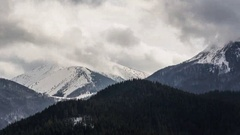 Heavy clouds in snowy mountains time lapse. Fast moving sky Stock Footage