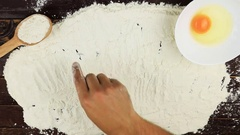 Top view Young man writes a word cake on white flour at wooden desk from above Stock Footage