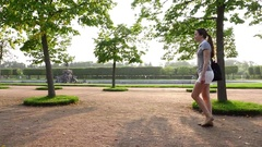 Young woman pace at beautiful parkland, sun flash through trees, tracking shot Stock Footage
