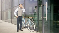 4K Businessman with bicycle leaving office building & talking on cell phone Stock Footage