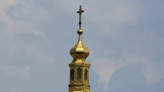 Orthodox Christian church dome topped with golden cross, cloudy sky background Stock Footage