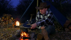 Сowboy pouring coffee in to the cup, sitting near campfire. Arkistovideo