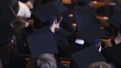 Young people in academic hats sitting at lecture hall, diploma awarding ceremony Stock Footage