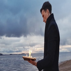 Young man reading burning book standing on coast storm clouds on background Stock Footage
