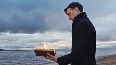 Young man with a burning book in hand standing on coast storm clouds on Stock Footage