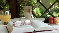 Still life with the book and glasses lying on a table in a garden Stock Footage