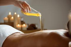 Honey pouring on girl's naked back in spa salon Stock Photos