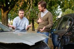Two men arguing after a car accident on the road Stock Photos