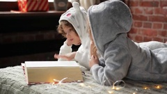 Children are dressed in warm xmas pajamas reading an interest book sitting on Stock Footage