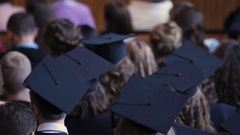 Many young men and women in academic caps sitting at university assembly hall Stock Footage