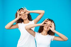 Two pretty girls twins smiling, joking over blue background Stock Photos