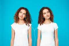 Girls twins listening music in headphones, smiling over blue background Stock Photos
