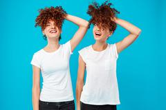 Two girls twins holding hair, joking over blue background Stock Photos