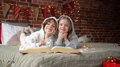Happy Cute little kids are dressed in warm xmas pajamas laughs and looking at Stock Footage