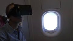 Woman using VR headset in the plane Stock Footage