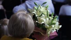 Elegant senior lady watching concert, holding bunch of beautiful lilium flowers Stock Footage