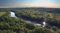 Drone view of reflective river next to trees and mountains 4 Stock Footage