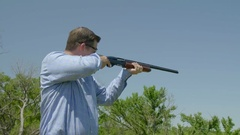 Person fires a gun skeet shooting Stock Footage