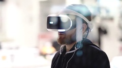 Bearded man uses VR-headset display with headphones for virtual reality game Stock Footage