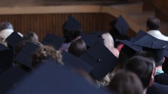 Many young people in academic hats sitting at assembly hall, graduation ceremony Stock Footage