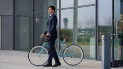 4K Businessman with bicycle leaving office at end of day & coworkers following Stock Footage