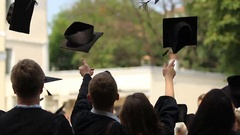 Happy young people throwing academic caps up, celebrating graduation, education Stock Footage