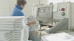 Worker in blue jacket worker puts the paper in the cutter guillotine machine in Stock Footage