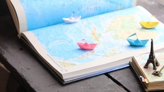 Tour Packages or Travel agent idea. Paper boats on the map and the Eiffel Tower Stock Footage