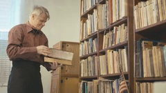 The old man flipping through the book in the room 4k Stock Footage