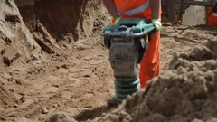 Worker compacting sand Stock Footage