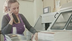Polygraph printing process - a woman speak telephone and make manual labor Stock Footage