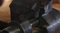 Man grinds metal part with a file in a vise close-up Stock Footage