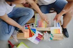 Two persons choose color of decor, sitting on a floor. Stock Photos