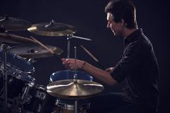 Side View Of Young Drummer Playing Drum Kit In Studio Stock Photos