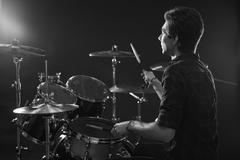 Black And White Shot Of Drummer Playing Drum Kit In Studio Stock Photos