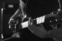 Close Up Of Man Playing Electric Guitar Shot In Monochrome Stock Photos