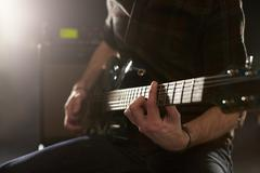 Close Up Of Man Playing Electric Guitar In Studio Stock Photos