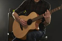 Close Up Of Man Playing Amplified Acoustic Guitar Stock Photos