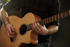Close Up Of Man Playing Acoustic Guitar In Studio Stock Photos