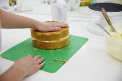 Close Up Of Woman In Bakery Preparing Cake For Decoration Stock Photos