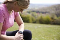 Mature Woman Checking Activity Tracker Whilst On Run Stock Photos