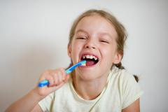 Cute little girl with pigtails diligently brushing his teeth. Stock Photos